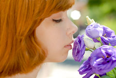 Young beautiful woman & chinese rose outdoors. Closeup portrait of a pretty sensual girl smelling purple flower of chinese rose outdoors on green spring or royalty free stock photos