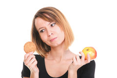 Young beautiful woman choose from sweet cake and red apple Stock Photos