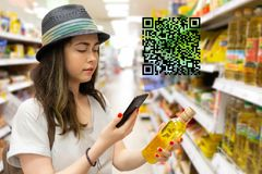 Young beautiful woman chooses a bottle of oil in the supermarket and checks the QR code on the label. The concept of modern stock image
