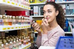 Young beautiful woman choosing fragrance Stock Photos
