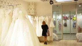 Young beautiful woman choosing a white gown in a wedding shop. Wed concept.  stock footage