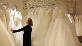 Young beautiful woman choosing a white gown in a wedding shop. Wed concept.  stock video footage