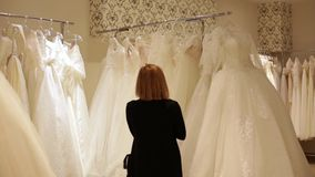 Young beautiful woman choosing a white gown in a wedding shop. Wed concept stock footage