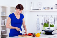 Beautiful woman is chopping vegetables in her modern kitchen. Young beautiful woman is chopping vegetables in her modern kitchen Stock Photo