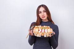 Young beautiful woman with chopsticks and sushi set, studio shoo stock photography