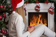 Girl with Christmas red hat warming legs near fireplace royalty free stock image