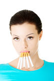 Young beautiful woman with cigarettes in mouth. Stock Images