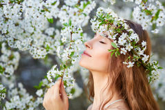 Young beautiful woman in circlet of flowers. Enjoying smell of blooming tree on a sunny day. Close eyes Stock Image