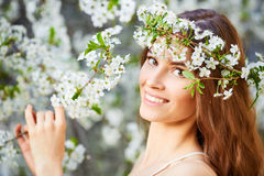 Young beautiful woman in circlet of flowers. Young beautiful woman in white dress in circlet of flowers Royalty Free Stock Photo