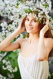 Young beautiful woman in circlet of flowers. Young beautiful woman in white dress in circlet of flowers Royalty Free Stock Photos