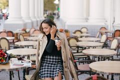 Young beautiful woman drinking coffee in a street cafe. Young beautiful woman in a classic trench coat drinking coffee in a street cafe stock images