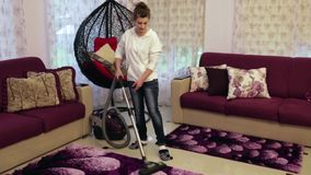Young beautiful woman cleans the house. Hoover carpet. Young beautiful woman cleans the house. Vacuuming the carpet stock video footage