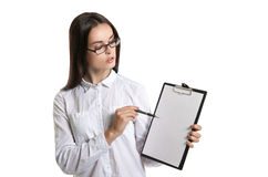 Young beautiful woman with a clipboard in his hands. Long-haired brunette in glasses and a white shirt. The woman points to the cl Stock Photography