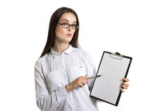 Young beautiful woman with a clipboard in his hands. Long-haired brunette in glasses and a white shirt. The woman points to the cl Stock Photo