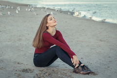 Young beautiful woman with closed eyes, long hair, in black jeans and red shirt, sitting on sand on beach among seagulls birds Stock Photos