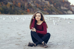 Young beautiful woman with closed eyes, long hair, wearing black jeans and red shirt, sitting on sand on beach among seagulls. Portrait of Caucasian young Royalty Free Stock Photos