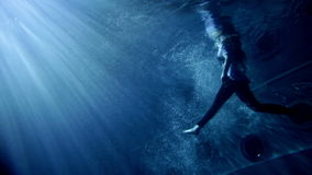 Young beautiful woman in clothes swimming under water. Underwater activity and young woman in clothes swimming under water stock footage