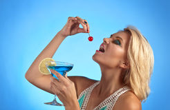 Young beautiful woman with cocktail on a blue background Stock Images