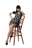 Young beautiful woman in cocktail dress is sitting on high woode Stock Images