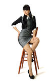 Young beautiful woman in cocktail dress is sitting on high woode. N chair Royalty Free Stock Image