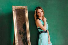 Young beautiful woman in cocktail dress standing near vintage mirror. With green empty wall on background, copyspace. Young beautiful woman in cocktail dress Stock Images