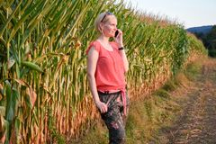 Young beautiful woman in colorful cloths and sunglasses outdoor talking on the cell phone royalty free stock image