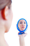 Young beautiful woman with colorful make up holding mirror. And looking at her reflection, isolated on white background Stock Images