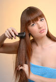 Young beautiful woman combing her hair Stock Photos