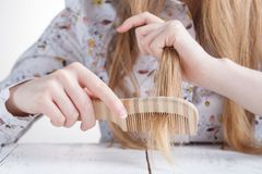 Young beautiful woman combing her hair in living room stock image