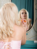 Young beautiful woman in a corset and stockings, applying makeup cosmetics in front of a mirror Royalty Free Stock Photography