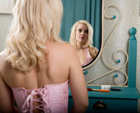 Young beautiful woman in a corset and stockings, applying makeup cosmetics in front of a mirror Royalty Free Stock Images