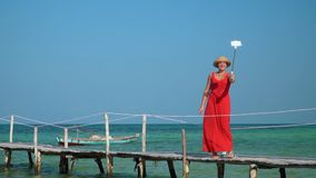 The young beautiful woman costs on a pier in the middle of turquoise transparent water. Bright sunny day on the island. On this video you can see as the woman in stock footage