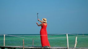 The young beautiful woman costs on a pier in the middle of turquoise transparent water. A pretty lady shoots a video of. On this video you can see as the woman stock footage