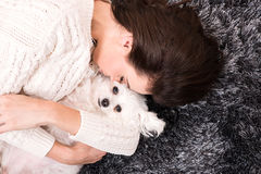 Young beautiful woman cuddling her Dog on the carpet Royalty Free Stock Images