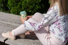 Girl with a cup of coffee on legs and sitting on a bench in a park on a sunny day royalty free stock photos