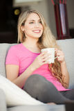 Young beautiful woman with a cup on sofa Stock Image