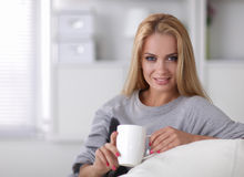 Young beautiful woman with a cup on sofa at home Stock Images