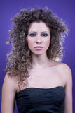 Young and beautiful woman, with curly hair. On purple background, studio shot Royalty Free Stock Images