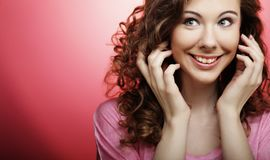 Young beautiful woman with curly hair over pink background. Close up Stock Photos