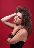 Young and beautiful woman, with curly hair, on red Royalty Free Stock Images