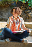 Young beautiful woman with curly hair thinking and writing in ex. Ercise book outside in park stock photography