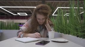 Young beautiful woman with red hair sits in a cafe and writes into a notebook stock video