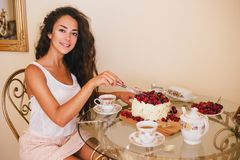 Young beautiful woman cuts cake at the kitchen. Young beautiful woman cuts cake with fresh berries and white icing at the kitchen Royalty Free Stock Photo