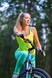 Young beautiful woman cycling on bicycle, summer park exercising Royalty Free Stock Photos