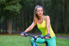 Young beautiful woman cycling on bicycle, summer park exercising Stock Photos
