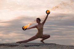 Young beautiful woman is dancing with fire wearing body suit on sunrise in the desert stock images