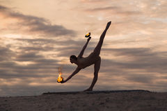 Young beautiful woman is dancing with fire wearing body suit on sunrise in the desert Stock Photos