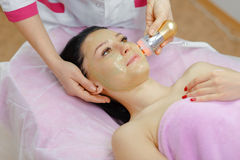 Young beautiful woman with dark hair gets procedure in the beauty salon Royalty Free Stock Image