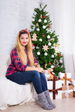 Young beautiful woman in decorated room with Christmas tree Royalty Free Stock Photography