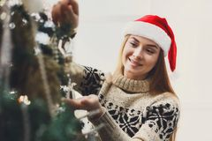 Young beautiful woman decorating christmas tree, new year decora Royalty Free Stock Images
